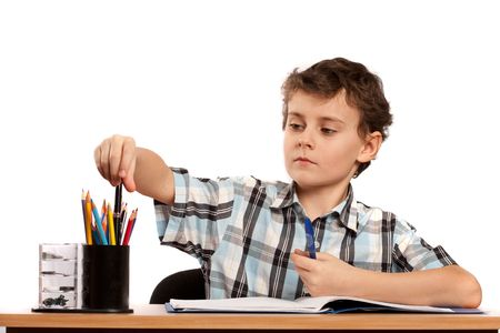 Portrait of a schoolboy doing homework at his desk, isolated on white background photo