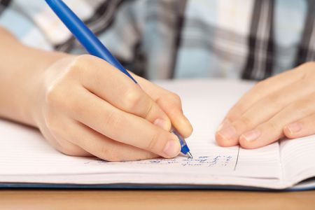 Close up of a hand of a pupil writing homework or examination photo