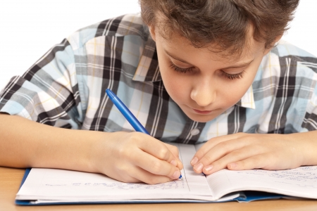 kids writing: Portrait of a schoolboy doing homework at his desk, isolated on white background Stock Photo