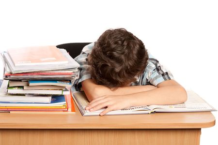 Portrait of a schoolboy sleeping on his desk near a pile of books Stock Photo