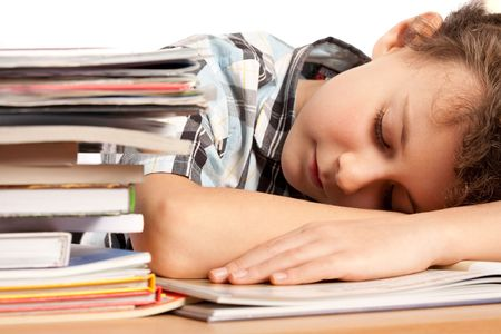 Portrait of a schoolboy sleeping on his desk near a pile of books photo