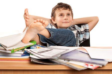 piedi nudi ragazzo: Ritratto di un scolaretto a piedi nudi con i suoi piedi fino sulla sua scrivania, in attesa di vacanza a venire Archivio Fotografico