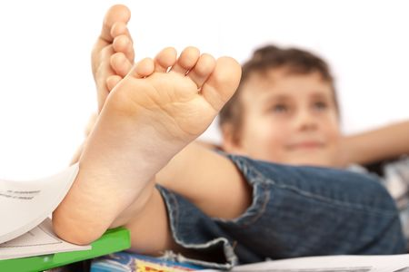 Portrait of a barefoot schoolboy with his feet up on his desk, waiting for holiday to come photo