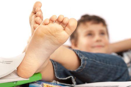 descalza: Retrato de un colegial descalzo con sus pies hasta en su escritorio, esperando de vacaciones venir