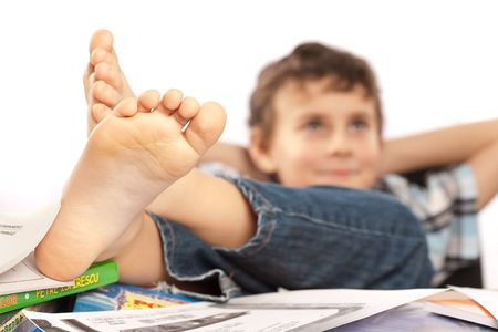 kid feet: Portrait of a barefoot schoolboy with his feet up on his desk, waiting for holiday to come Stock Photo