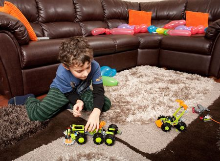 inventive: Child playing with plastic trucks on the floor
