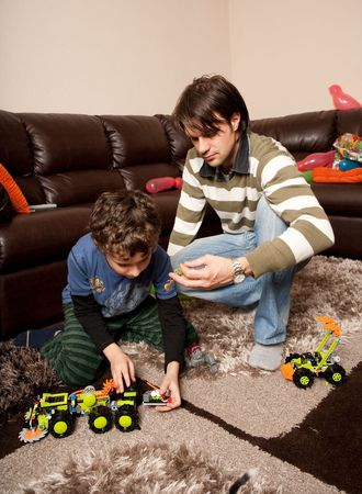 kneeled: Older brother playing with little brother with plastic trucks indoor