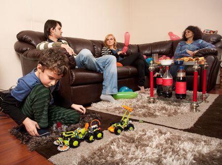 Child playing on the floor with plastic trucks while the adults are chatting on the sofa
