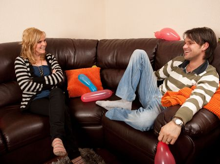 Two people chatting on the sofa at a party photo