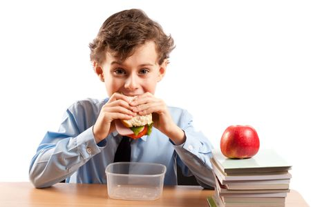 pause repas: Schoolboy ayant un sandwich et une pomme pendant sa pause d�jeuner