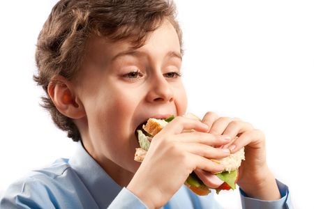 Schoolboy having a sandwich during his lunch break photo