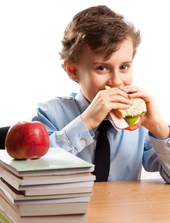 Schoolboy having a sandwich and an apple during his lunch break photo