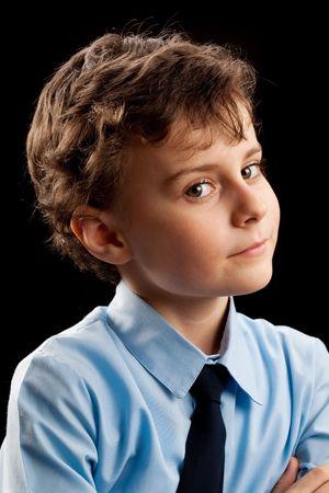 Portrait of a suspicious schoolboy isolated on black background Stock Photo - 6395057