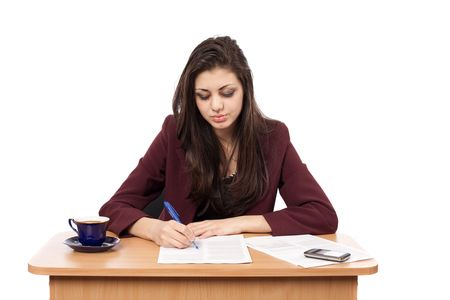 Young businesswoman writing some documents at her desk photo