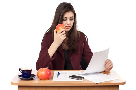 Young businesswoman in her lunch break eating an apple while reading documents photo