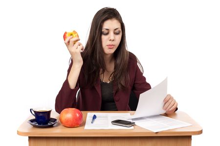 latinamerican: Young businesswoman in her lunch break eating an apple while reading documents