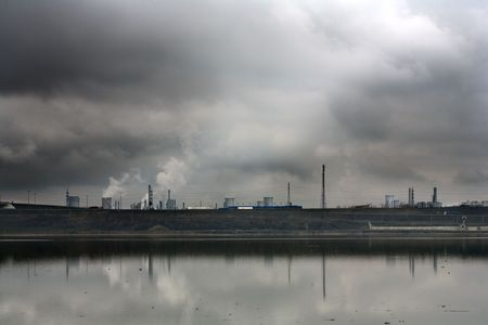 Landscape with refinery near  polluted river in a cloudy day photo