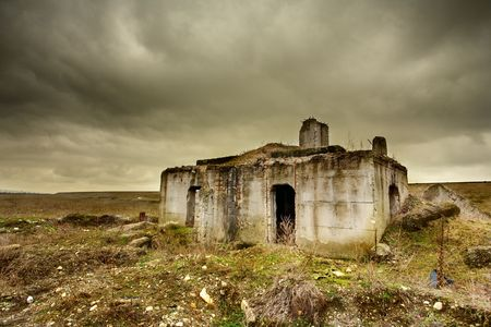 Landscape with a decrepit ruin of a building under moody sky