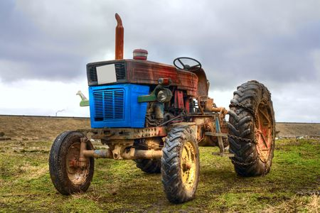 Image of an abandoned vintage tractor on a grass field photo