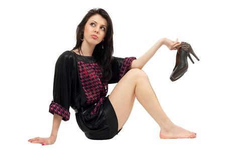 high life: Beautiful caucasian brunette barefoot, holding her high heels shoes