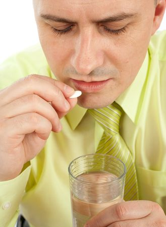 Young businessman with headache taking a pill
