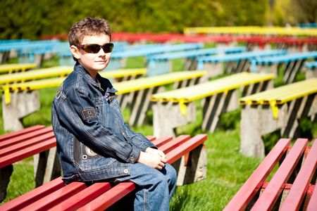 Cool and trendy boy sitting on a bench in a park photo