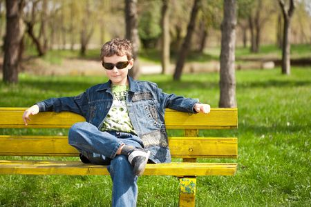 Cool and trendy little boy sitting on a bench in park photo