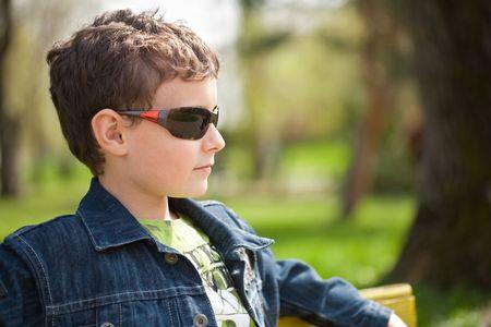 Closeup portrait of a trendy little boy outdoor photo
