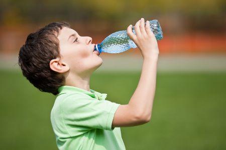 sediento: Retrato de un niño lindo que bebía agua de una botella al aire libre