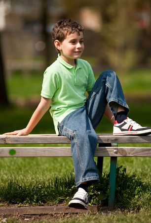 Portrait of a cute little boy sitting on a bench in a park photo