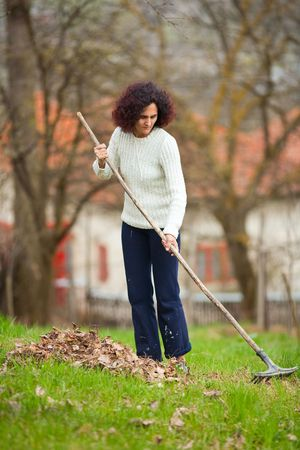 Young redhead pretty country girl using a rake to clean up of the fallen leaves Stock Photo - 6792662