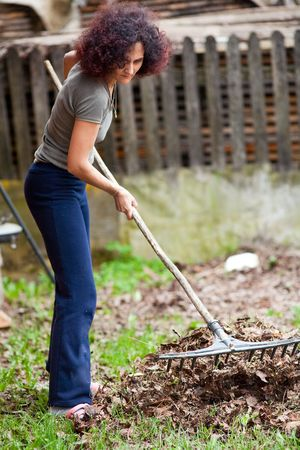 Young redhead pretty country girl using a rake to clean up of the fallen leaves Stock Photo - 6792655
