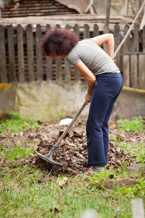 Young redhead pretty country girl using a rake to clean up of the fallen leaves Stock Photo - 6792652