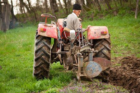 ploegen: Senior landbouw producent met gebruikmaking van een oude tractor te ploegen zijn land  Stockfoto