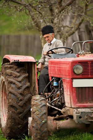 Senior farmer using an old tractor to plow his land photo