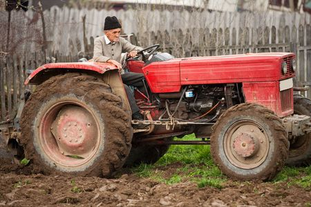 Senior farmer using an old tractor to plow his land Stock Photo
