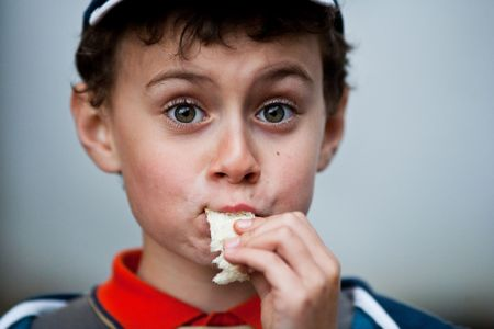 Close up portrait of a funny kid eating bread