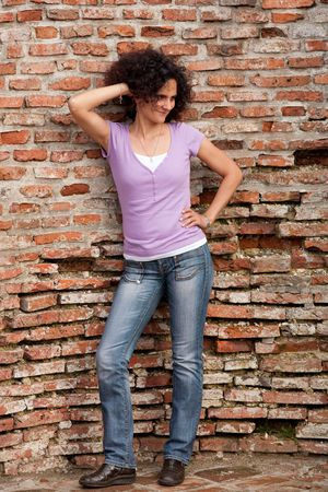 Full length portrait of a redhead woman with curly hair near a brick wall photo