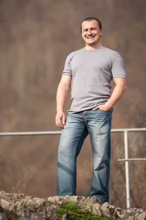 Full length portrait of a young caucasian man outdoors photo