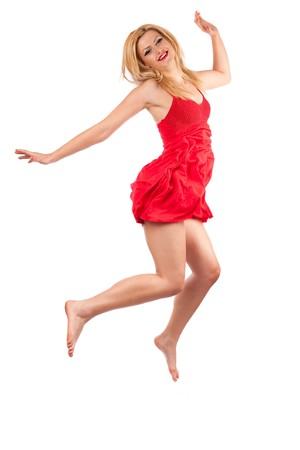 Barefoot young lady in red dress jumping in the air, isolated on white photo