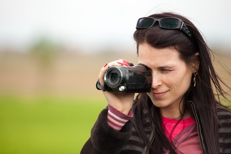 Portrait of a young brunette woman using a camcorder outdoors photo