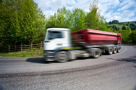 Big truck with trailer speeding on a road, with motion blur photo