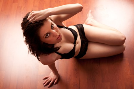 Gorgeous caucasian girl in lingerie sitting on wooden floor and looking up photo