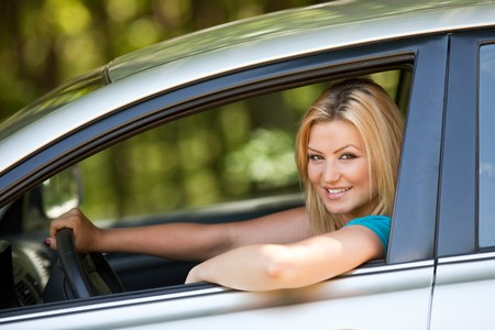 Attractive blonde young woman at the wheel in her new car Stock Photo