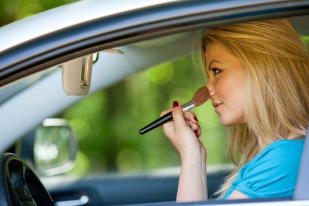 Young blonde woman applying makeup while in the car photo