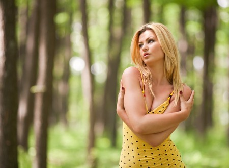 Beautiful blonde woman in yellow dress in the forest photo