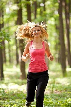 Blonde young lady running through the forest photo