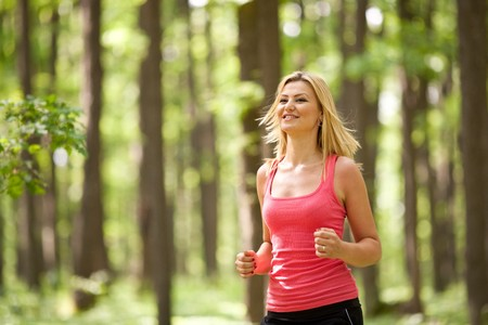 Blonde young lady running through the forest Stock Photo