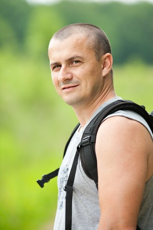 Close up of a young man with backpack and t-shirt hiking into the woods photo