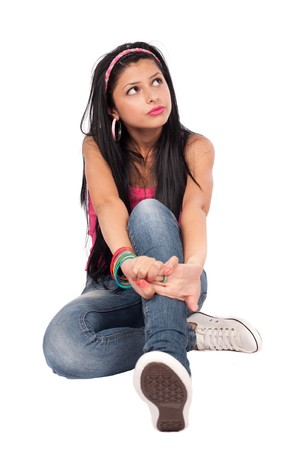 legs folded: Portrait of a beautiful teenager sitting, isolated on white background